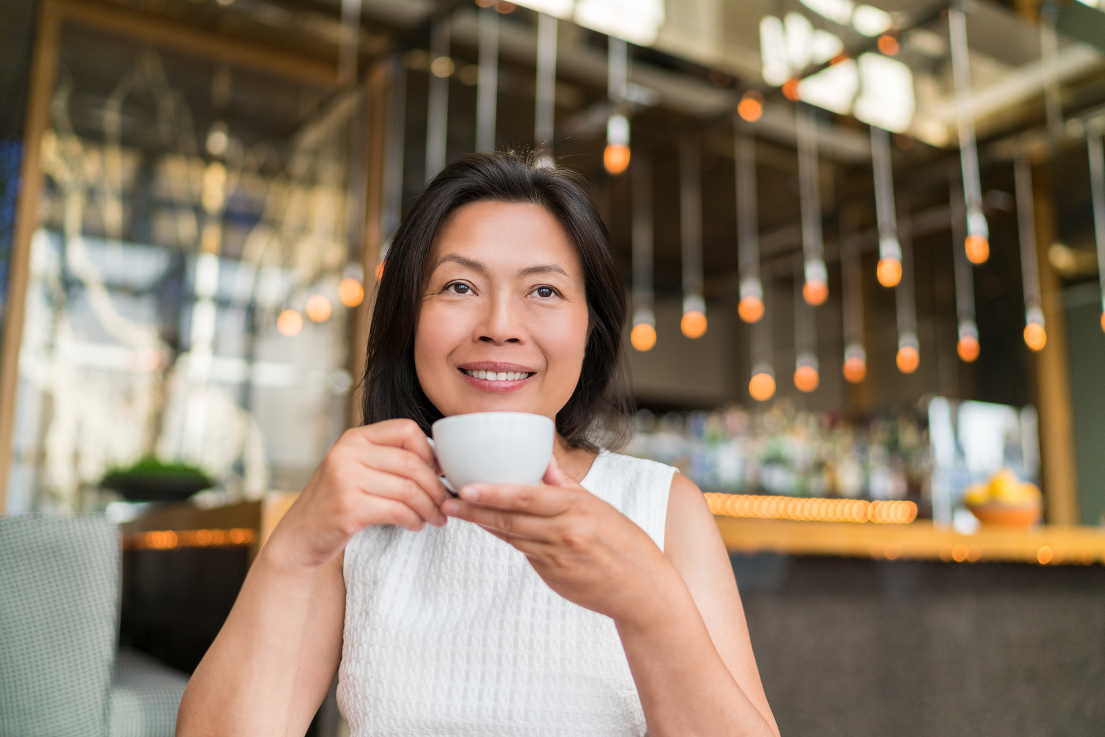 Asian middle aged woman drinking cappuccino coffee at high end f